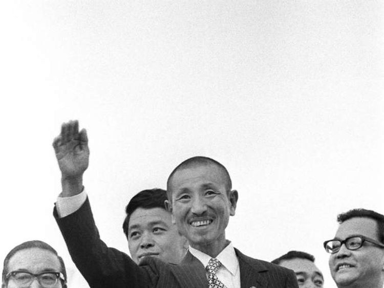 Former Japanese imperial army soldier Hiroo Onoda (C) waving upon his return home