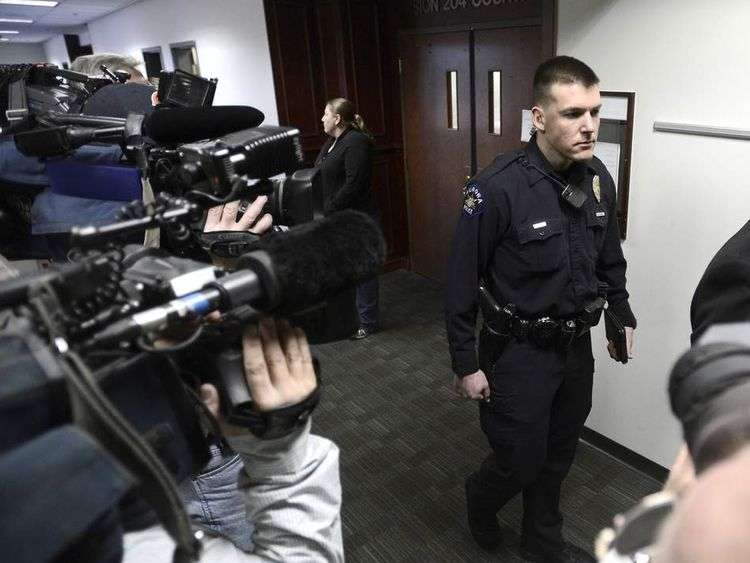 Aurora police officer Jason Oviatt (R) leaves court