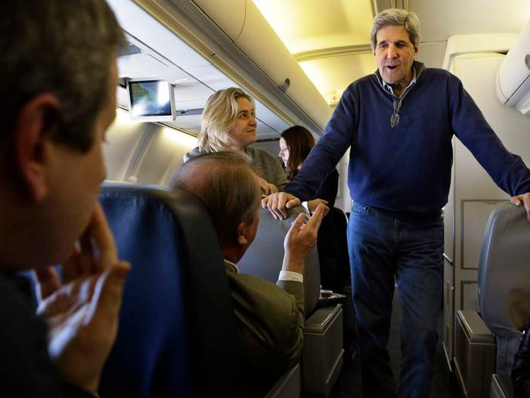 U.S. Secretary of State John Kerry speaks to media personnel aboard a plane that is en route to London on his inaugural official trip as Secretary