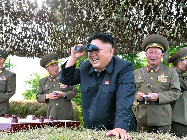 KCNA handout shows North Korean leader Kim Jong Un looking through a pair of binoculars during inspection of Hwa Islet Defence Detachment off east coast of Korean peninsula