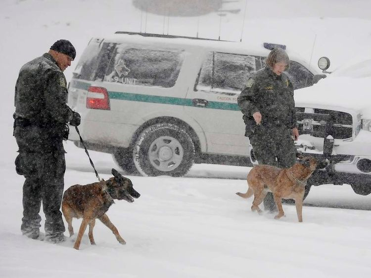 Law enforcement officers get their search dogs warmed up to continue the search for Christopher Dorner in the heavy snow at the Bear Mountain ski resort at Big Bear Lake