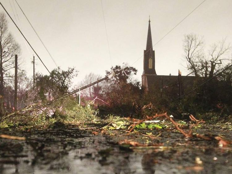 Downed trees and power lines caused by a Christmas Day tornado are seen along Dauphin Street in Mobile