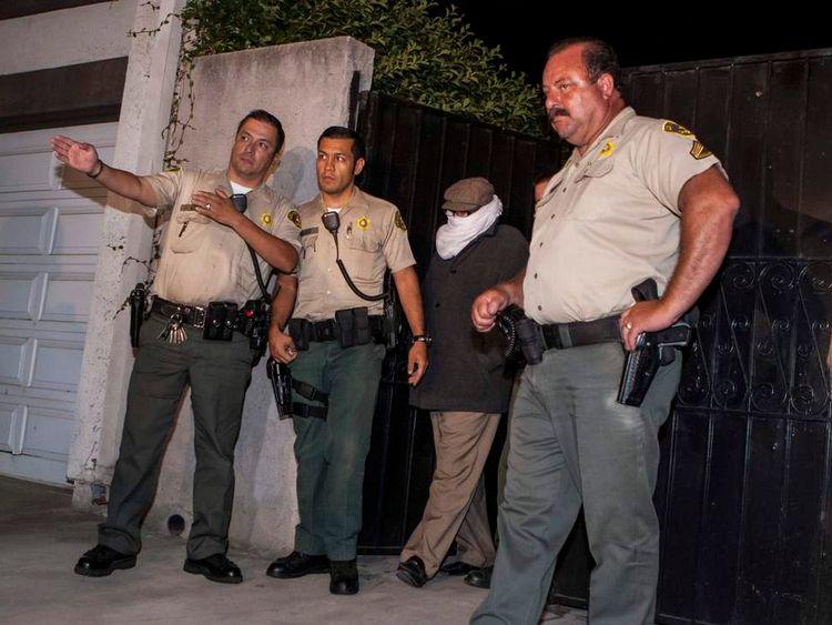 Nakoula Basseley Nakoula flanked by police officers