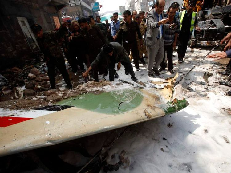 The wing of a military aircraft is being pulled at the site of its crash by a police vehicle in Sanaa
