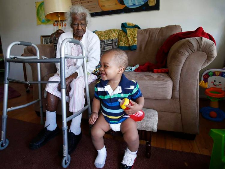 Talley watches her 14-month-old great-great-grandson Armmell Holloway plays next to her during her 115th birthday in her home in Inkster