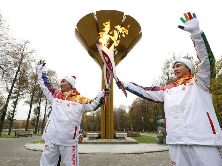 Student Anatoly Chentuloev and journalist Yeon Kyu-sun take part in the Sochi 2014 Winter Olympic torch relay in Moscow