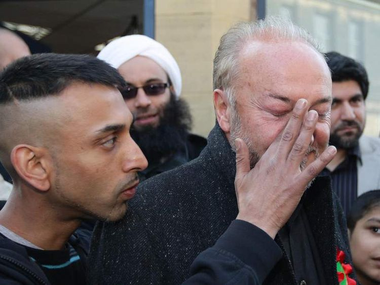 A supporter of MP George Galloway wipes his face after an egg was thrown towards the MP