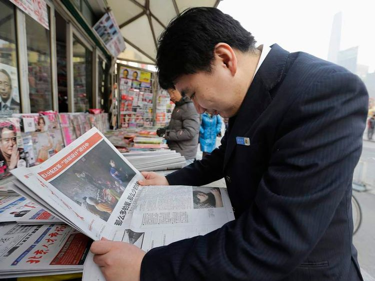 A man reads the cover story of the Southern Weekly at a newsstand in Beijing