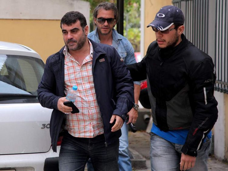 Greek journalist Kostas Vaxevanis (L)  is escorted by plain-clothed police officers to the public prosecutor in Athens on October 28, 2012, following his arrest after publishing names from a list of Greeks with Swiss bank accounts in his magazine.
