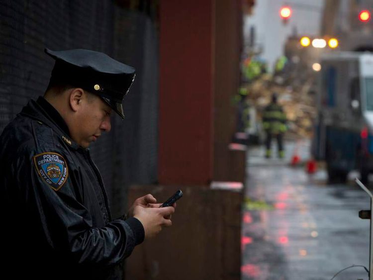 A New York police officer looks at his phone in the rain, following the collapse of two buildings in the Manhattan borough of New York