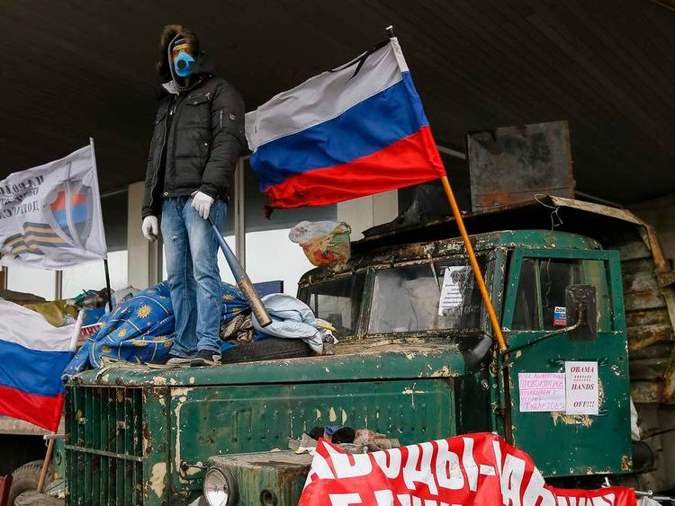 A pro-Russia protester stands at a barricade outside a regional government building in Donetsk