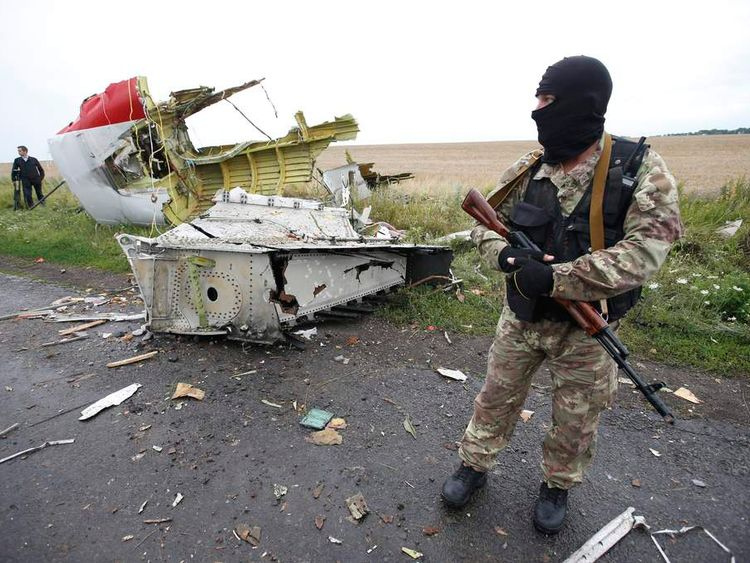 A pro-Russian separatist stands at the crash site of Malaysia Airlines flight MH17, near the settlement of Grabovo in the Donetsk region