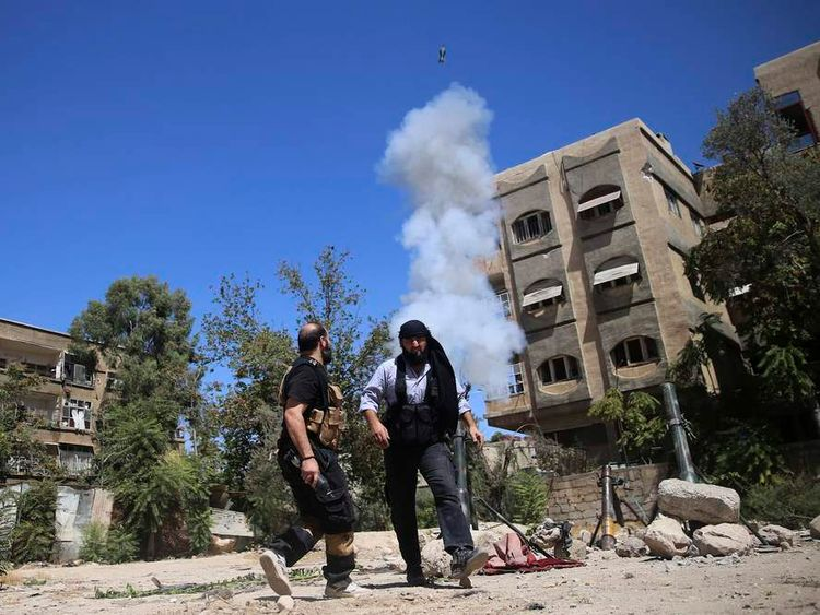 Members of the 'Ansar Dimachk' Brigade which operates under the Free Syrian Army, fire a homemade mortar on one of the battlefronts in Jobar