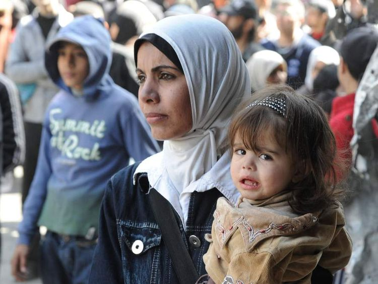 Residents wait to receive food aid distributed by the UN at the besieged al-Yarmouk camp