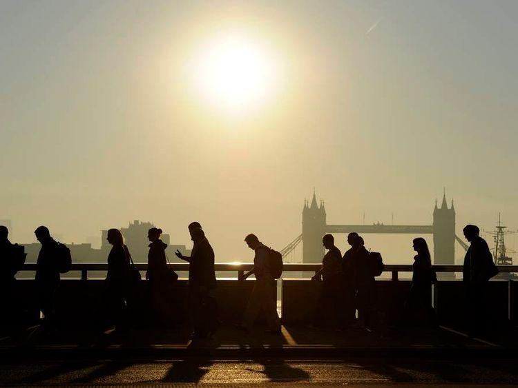 Workers cross London Bridge, with Tower Bridge seen behind,