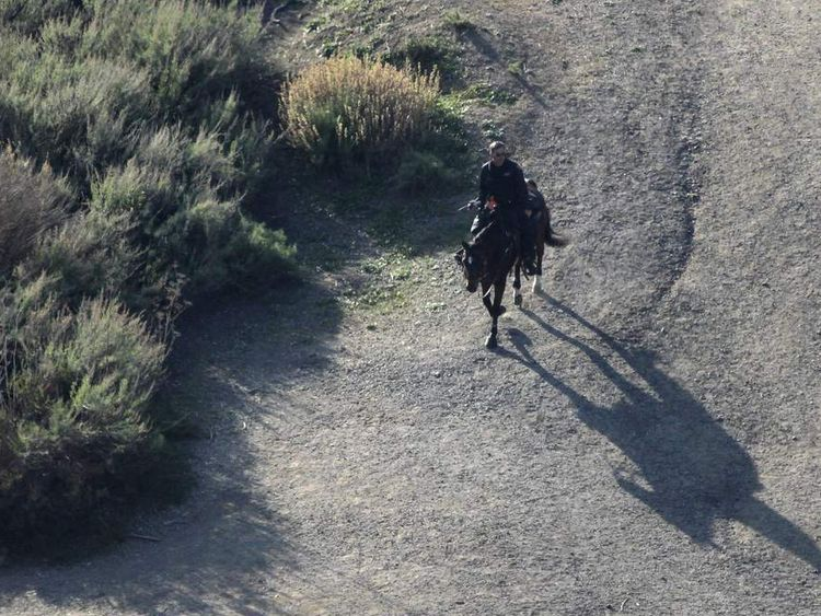 January 2012: A LAPD mounted police officer searches a hilly area below the iconic Hollywood sign in Los Angeles