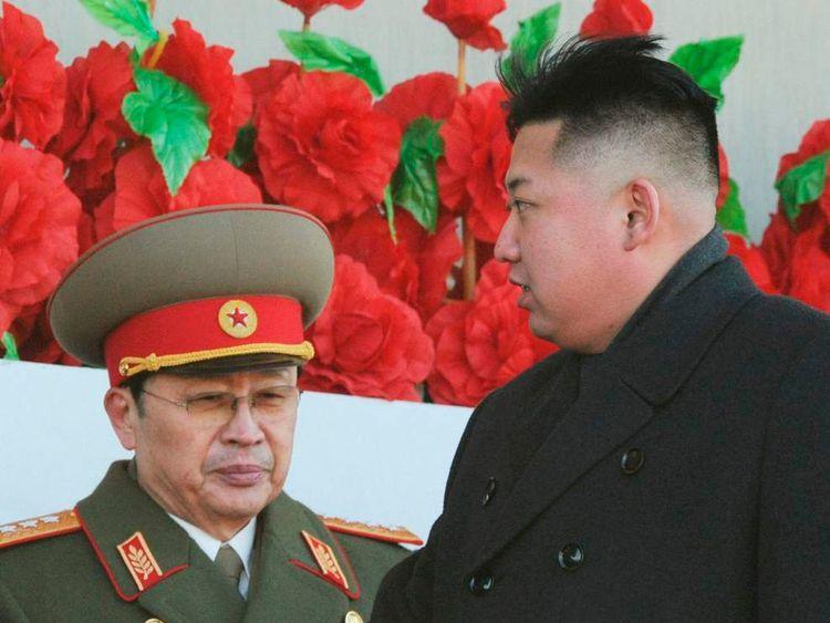 North Korean leader Kim Jong-un, flanked by his uncle North Korean politician Jang Song-thaek, leaves a military parade in Pyongyang
