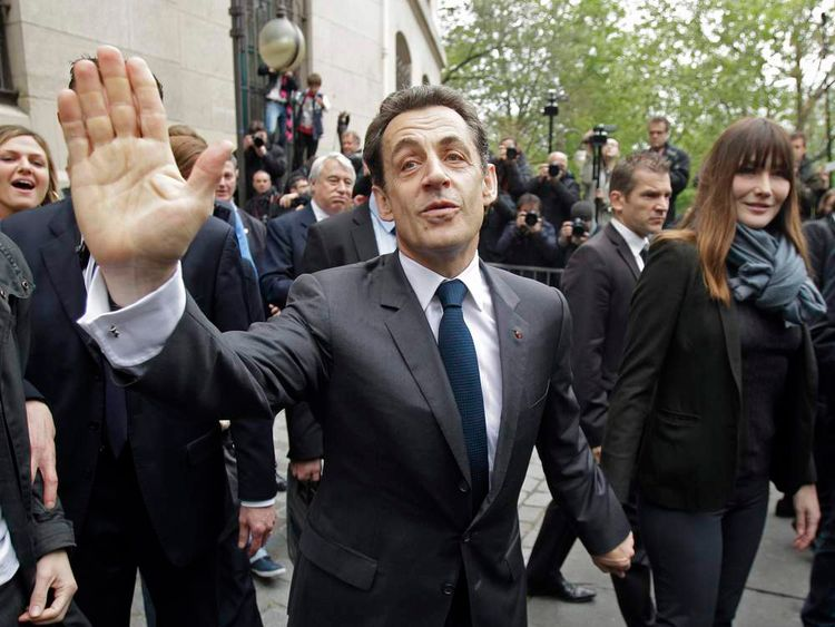 Nicolas Sarkozy, France's President and UMP party candidate for his re-election, and his wife Carla Bruni-Sarkozy leave after voting in the second round in Paris