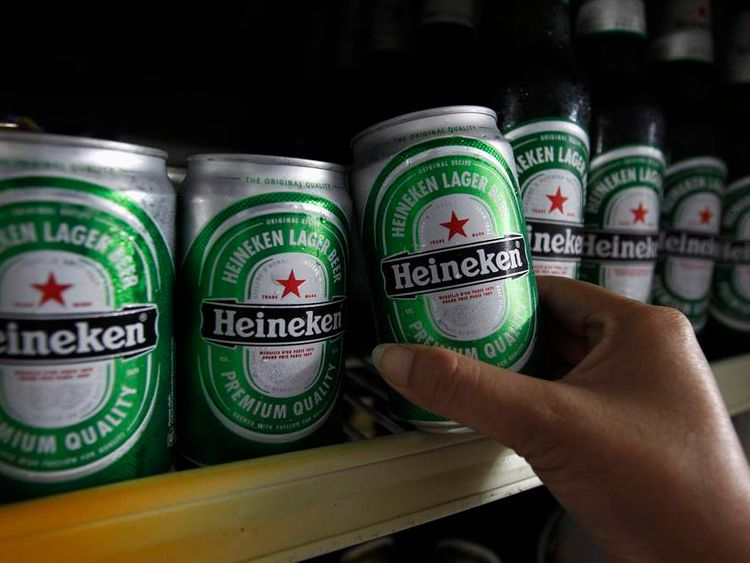 Woman reaches for a can of Heineken at a restaurant in Bangkok