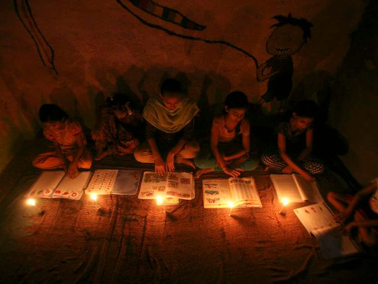 A lesson by candlelight after a power cut in India