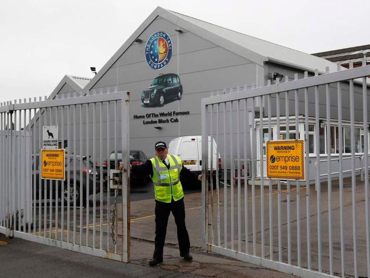 A security guard closes the main gate of the London Taxi Company in Coventry