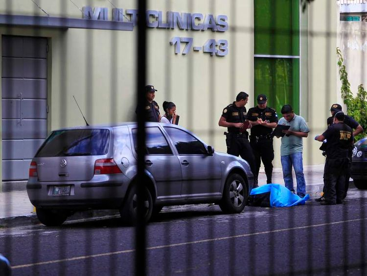 Police officers stand next to the body of a man at a crime scene outside a private clinic in Guatemala City