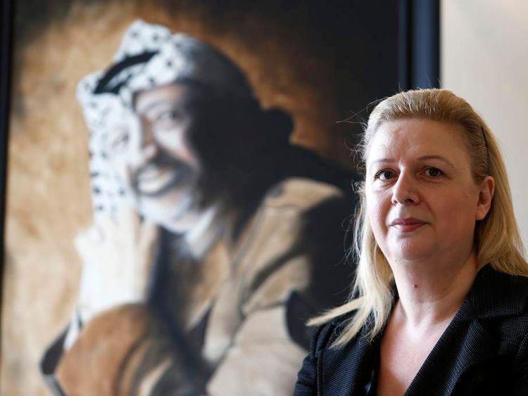 Suha Arafat poses near a portrait of her late husband and Palestinian leader Yasser Arafat