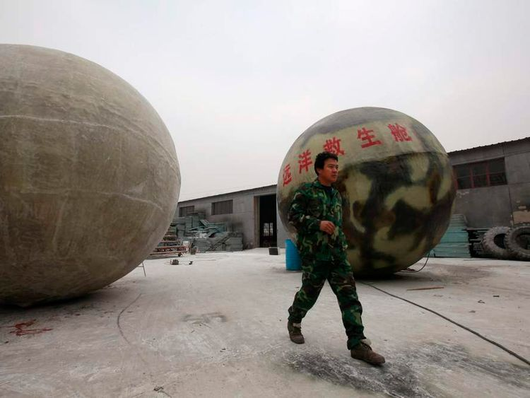 Chinese inventor Liu walks past his spherical pods, named Noah's Ark