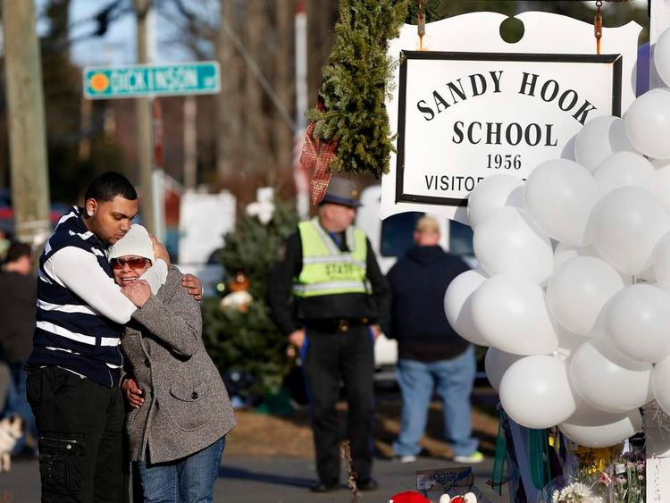 People grieve next to a makeshift memorial of flowers and balloons next to the Sandy Hook Elementary school sign in Sandy Hook