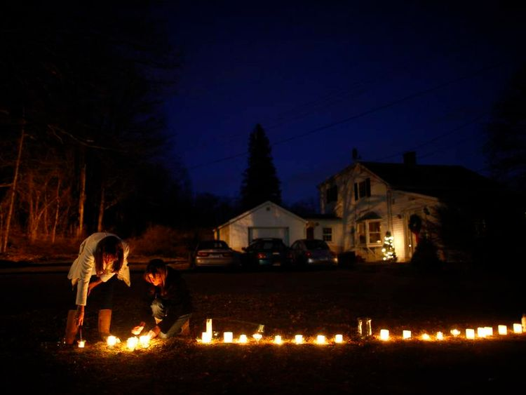 Women light candles for victims near Sandy Hook Elementary School in Newtown