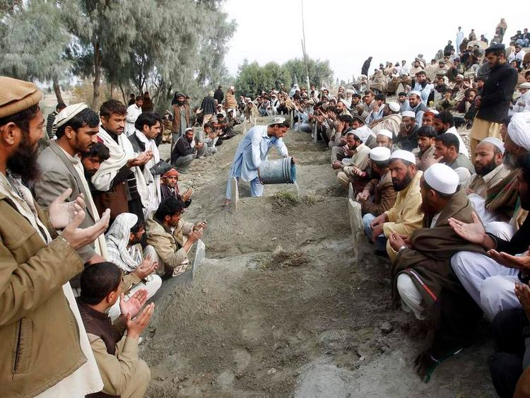 Afghan villagers pray over the graves of girls who were killed by an explosion in Jalalabad