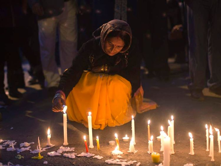 A demonstrator lights candles during a candlelight vigil for a gang rape victim who was assaulted in Delhi