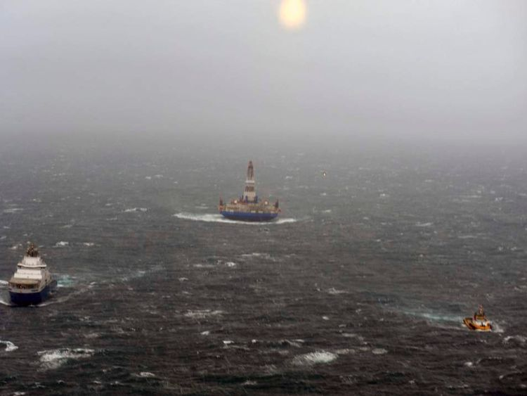 The tow vessel Aiviq and the tug Alert tow the conical drilling unit Kulluk through rough seas southeast of Kodiak