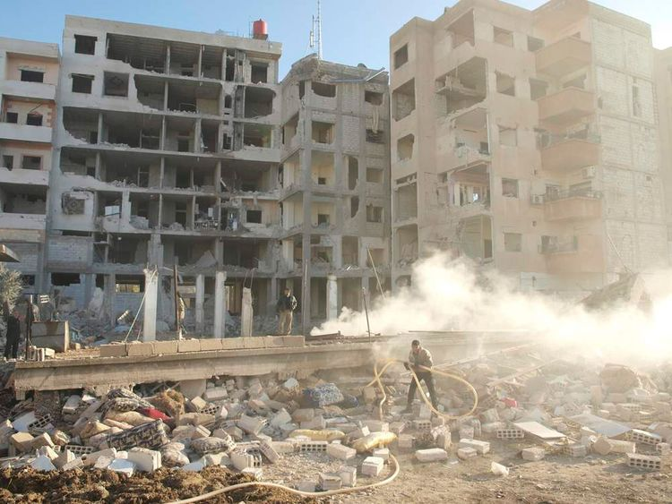 Residents stand near damaged buildings in Daraya