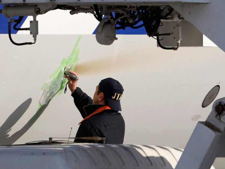 A member of JTSB inspects a small spot of black soot on the body of the All Nippon Airways' (ANA) Boeing Co's 787 Dreamliner plane which made an emergency landing on Wednesday, at Takamatsu airport in Takamatsu