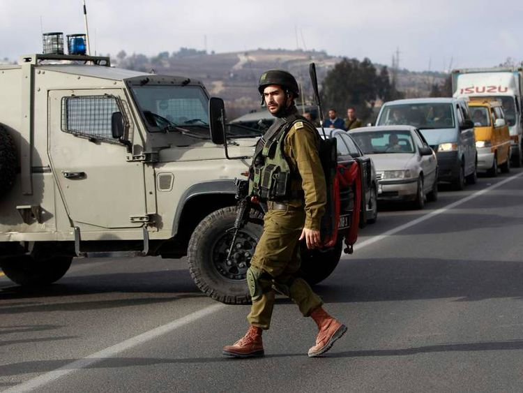 An Israeli soldier walks in front of a military vehicle near the scene of a shooting in al-Arroub refugee camp near Hebron