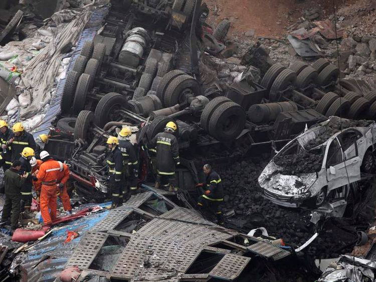 Rescuers look for survivors near a wreckage of vehicles after an expressway bridge partially collapsed on the Lianhuo highway in Mianchi county