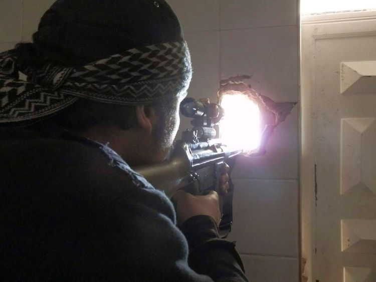 A member of the Free Syrian Army points his weapon through a hole in a wall in Daraya