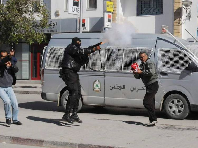 A police officer fires teargas to break up a protest during a demonstration in Gafsa