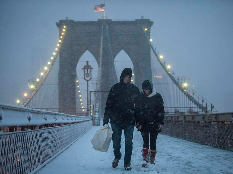 A couple crosses the Brooklyn Bridge through snow and wind in New York