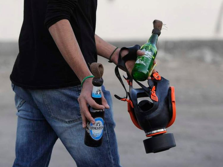 An anti-government protester walks with molotov cocktails and a gas mask prior to clashes with riot-police in Budaiya