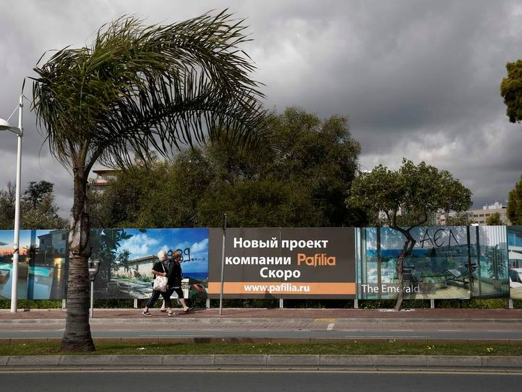 Two women make their way alongside Russian advertisements about a property development in Limassol, a coastal town in southern Cyprus
