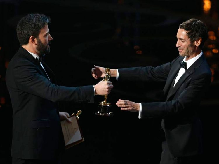 """Malik Bendjelloul receives his Oscar for best documentary for """"Searching for Sugar Man"""" from presenter Affleck at the at the 85th Academy Awards in Hollywood."""