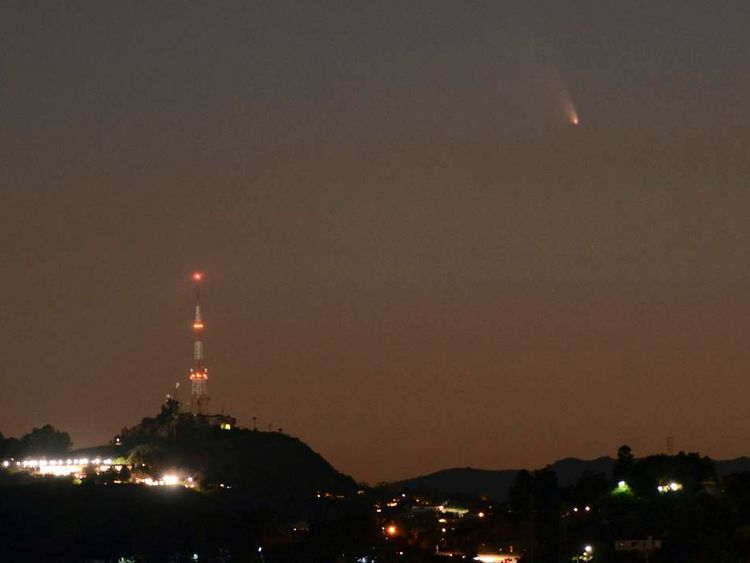 The comet PANSTARRS is seen next to the waxing crescent moon off the western coast of Southern California, in Los Angeles