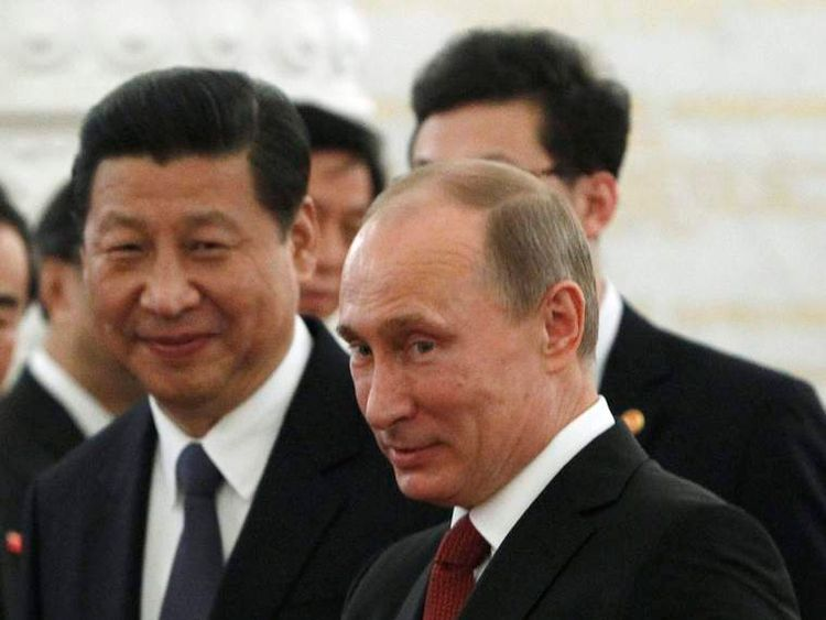 Russia's President Putin gestures as his Chinese counterpart Xi smiles
