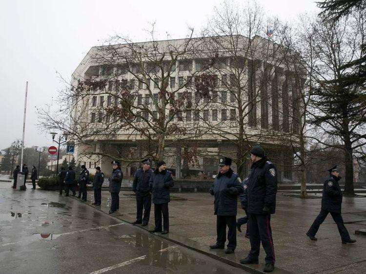 Ukrainian police stand guard in front the Crimean parliament building in Simferopol