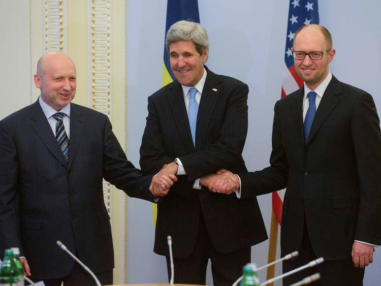 Ukrainian Prime Minister Arseny Yatseniuk (R), U.S. Secretary of State John Kerry (C) and Ukraine's acting President Oleksander Turchinov join hands during their meeting in Kiev