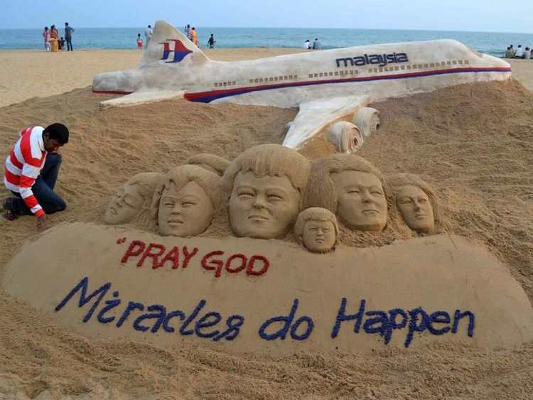 Indian sand artist Patnaik applies final touches to a sand art sculpture he created wishing for the well being of the passengers of Malaysian Airlines flight MH370, on beach in Puri, in the eastern Indian state of Odisha