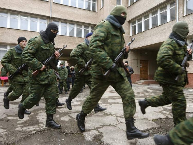 Members of a pro-Russian self defence unit run after taking an oath to Crimea government in Simferopol