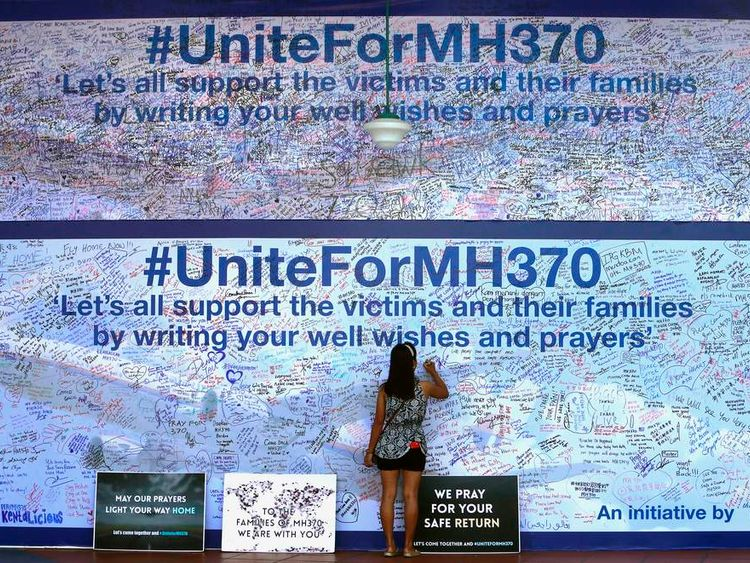 A woman writes a message on a board dedicated to passengers onboard the missing Malaysia Airlines Flight MH370 and their family members